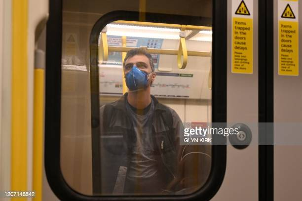 Man wearing a mask stands in an underground train in London on March 14, 2020. - British Prime Minister Boris Johnson, who has faced criticism for...