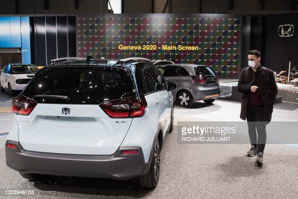Man wearing a mask stands near a car on February 28, 2020 at the Geneva International Motor Show which has been cancelled due to the Covid-19...