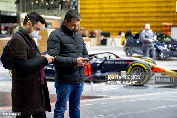 A man wearing a mask stands near a car on February 28 2020 at the Geneva International Motor Show which has been cancelled due to the Covid19...
