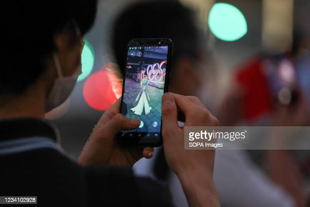 Man wearing a mask takes a photo of Olympic Rings installation at the Nihonbashi bridge in Tokyo. 'Despite the controversy about the Tokyo 2020...
