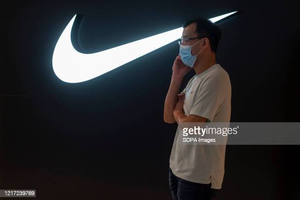 Man wearing a mask talks on the phone while wearing a face mask in front of the American multinational sport clothing brand Nike store and logo seen...