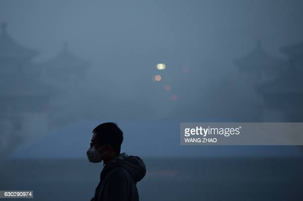 TOPSHOT A man wearing a mask visits a park amid heavy air pollution in Beijing on December 20 2016 Beijing issued its first air pollution red alert...
