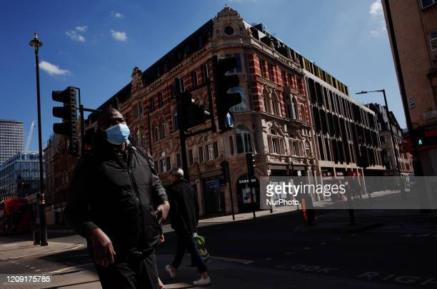 Man wearing a mask walks along a near-deserted Oxford Street in London, England, on April 4, 2020. Across the UK a total of 41,903 cases of the...