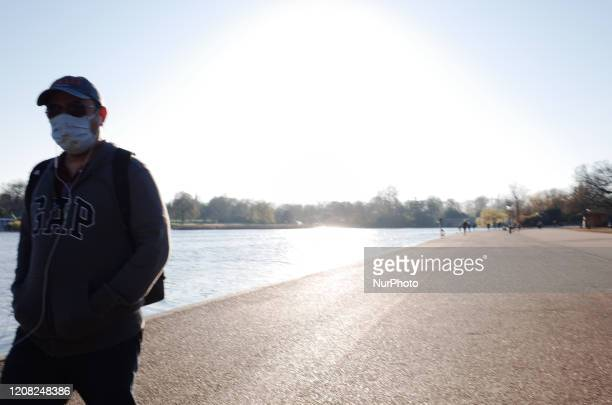 A man wearing a mask walks beside the Serpentine lake in Hyde Park in London England on March 25 2020 Around a largely shutdown country the covid19...