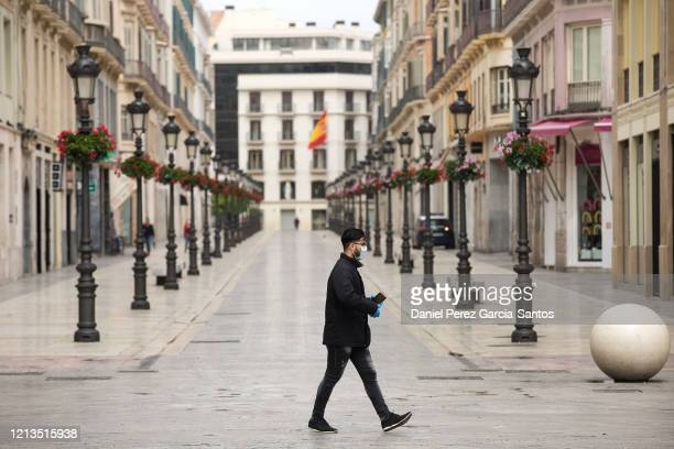 Man wearing a mask walks on the fourth working day of the lockdown caused by the coronavirus pandemic on March 19, 2020 in Malaga, Spain. The...
