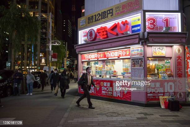 Man wearing a mask walks past a lottery ticket shop in Shinbashi district of Minato in Tokyo.