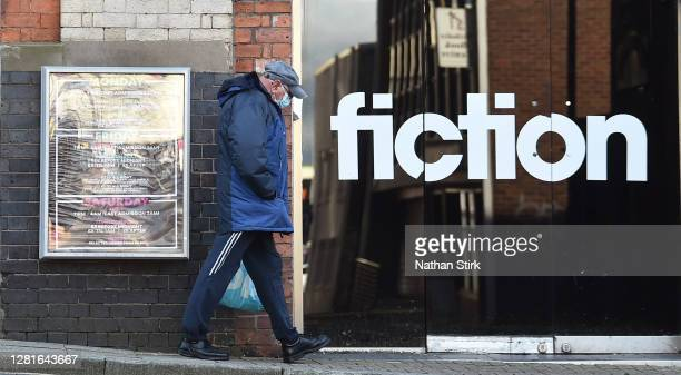 A man wearing a mask walks past a Nightclub called Fiction as StokeonTrent prepares to move up to High Covid Alert Level on October 22 2020 in Hanley...