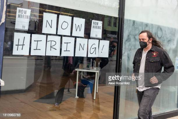 """Man wearing a mask walks past a """"now hiring"""" sign on Melrose Avenue amid the coronavirus pandemic on April 22, 2021 in Los Angeles, California. Los..."""
