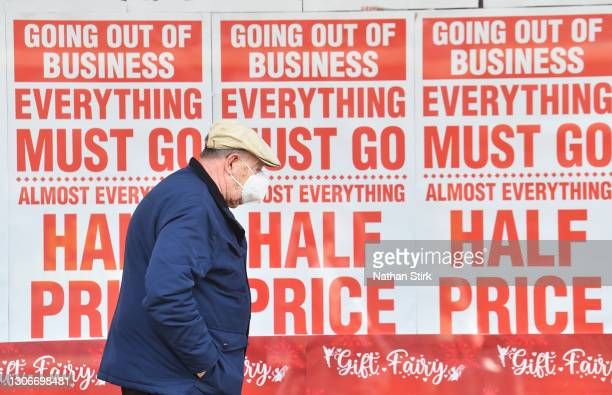 Man wearing a mask walks past a sign in a shop window saying 'going out of business, everything must go' on March 12, 2021 in Stockport, England.