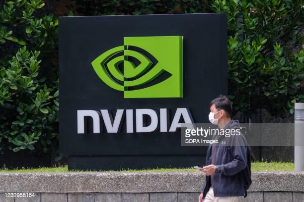 Man wearing a mask walks past an Nvidia logo in Taipei.