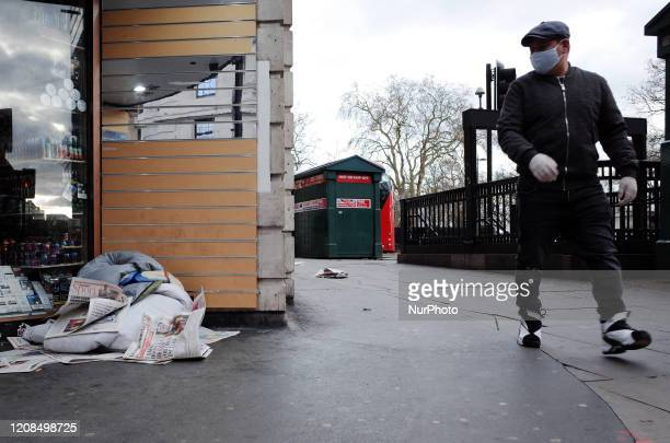 Man wearing a mask walks past the belongings of a homeless person in a doorway at the Marble Arch end of Oxford Street in London, England, on March...