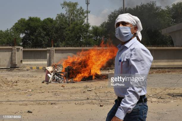 Man wearing a mask walks past the burned chinese products during a protest against Chinese President Xi Jinping in Gurugram on the outskirts of New...