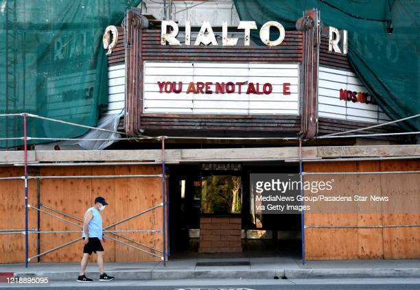 """Man wearing a mask walks past the Rialto Theatre along Fair Oaks Ave. As the marquee reads You Are Not Alo e as the """"N"""" for Alone has fallen out in..."""