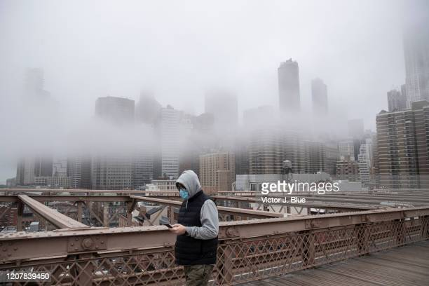 A man wearing a mask walks the Brooklyn Bridge in the midst of the coronavirus outbreak on March 20 2020 in New York City The economic situation in...