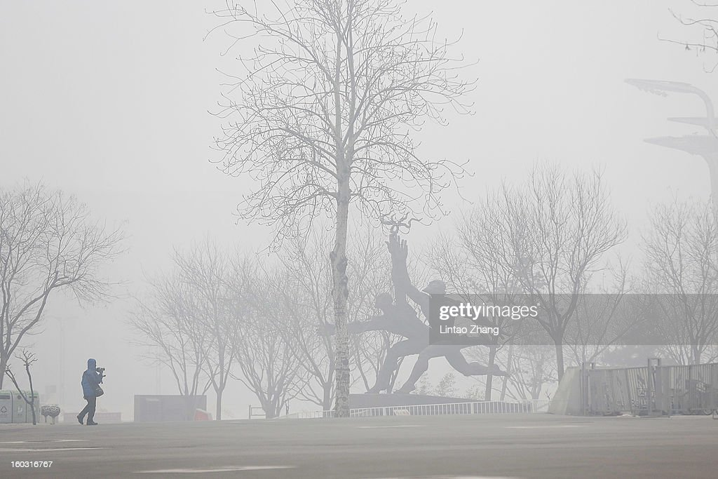 A man wearing a mask walks through fog as severe pollution continues to affect the capital on January 29, 2013 in Beijing, China. China's ruling Communist party has announced temporary emergency measures in an attempt to combat the current hazardous levels of pollution enveloping Beijing.
