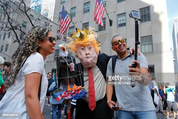 A man wearing a mask with the face of President Trump poses in front of St Patrick's Cathedral during the annual Easter Parade and Easter Bonnet...