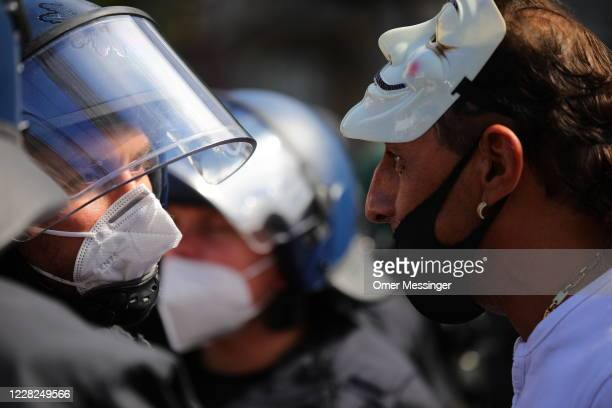 Man wearing a masquerade mask on his head speaks to a police officer as coronavirus skeptics and right-wing extremists march in protest against...