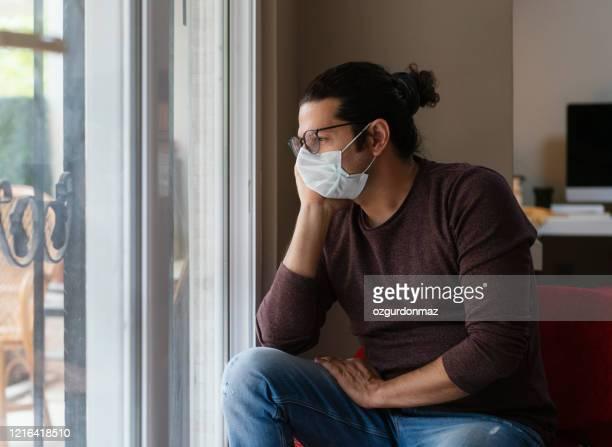 homem usando máscara médica fica em casa sob quarentena durante surto de coronavirus - questão social - fotografias e filmes do acervo