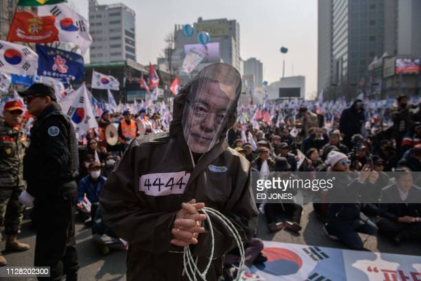 Man wearing a Moon Jae-in mask stands with conservative right-wing pro-US protesters during a rally denouncing government policies towards North...