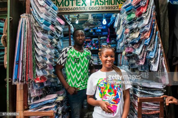 A man wearing a Nigerian World Cup jersey poses for a photo in one of the alleyways in Balogun Market in Lagos on June 14 2018 The Nigeria Super...