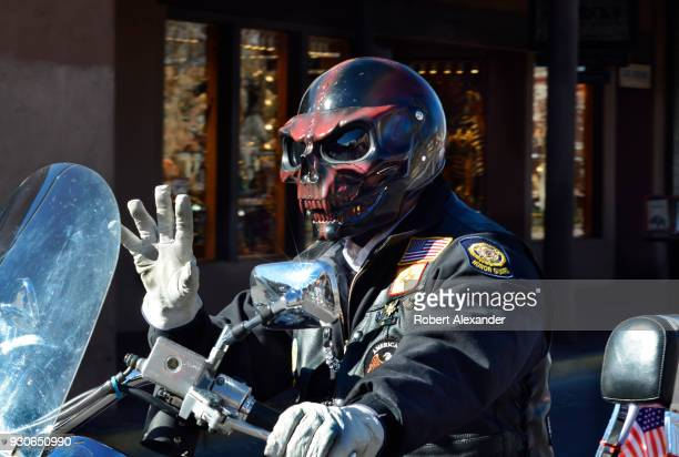 A man wearing a novelty monster or skull helmet rides his motorcycle in a Veterans Day parade in Santa Fe New Mexico