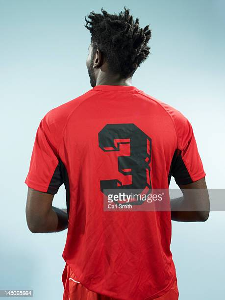 a man wearing a numbered soccer shirt - fußballtrikot stock-fotos und bilder