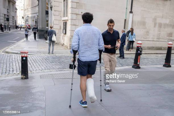 Man wearing a plaster cast and using mobility aids, hobbles past another male wearing a foot boot in the City of London, the capital's financial...