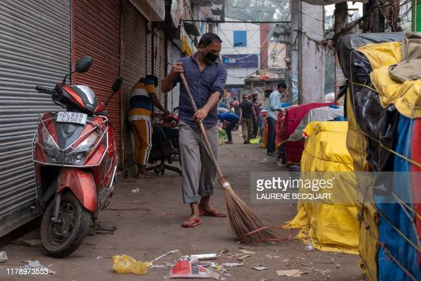 A man wearing a pollution mask sweeps a street with a broom in the old quarters of New Delhi on October 30 2019
