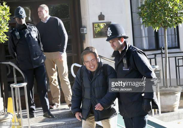 A man wearing a Prince William Duke of Cambridge mask is escorted away by a police officer from the King Edward VII Private Hospital on December 4...
