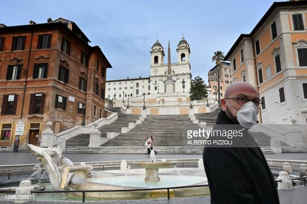 Man wearing a protection mask walks by the Spanish Steps at a deserted Piazza di Spagna in central Rome on March 12 as Italy shut all stores except...