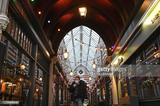 Man wearing a protective face covering to combat the spread of the coronavirus, walks through a shopping arcade in Hull, in north-east England on...