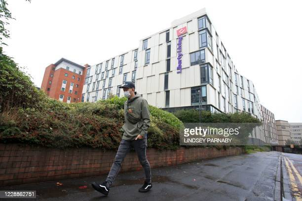 Man wearing a protective face covering walks past halls of residence for students in Newcastle-upon-Tyne, north-east England on October 3 as many...