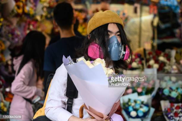 A man wearing a protective face mask as a preventative measure against the COVID19 coronavirus buys flowers to mark Valentine's Day in Hong Kong on...