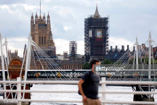 Man wearing a protective face mask crosses Waterloo Bridge with the Palace of Westminster behind in central London on August 24, 2020. - For those...