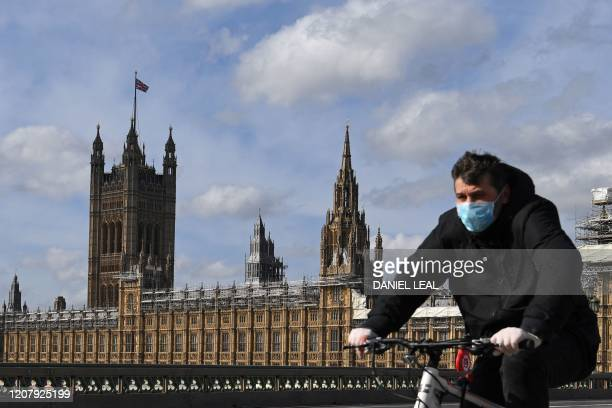 A man wearing a protective face mask cycles across Westminster Bridge with the Houses of Parliament behind in central London on March 21 a day after...