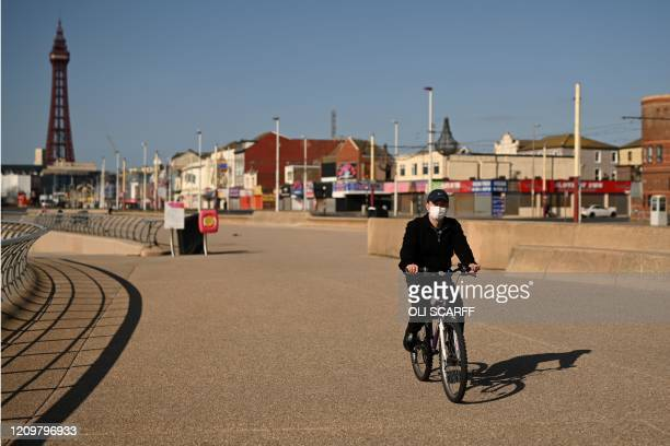 Man wearing a protective face mask cycles along the promenade away from the tower enjoying the spring sunshine on the coast in Blackpool, north-west...