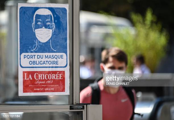 Man wearing a protective face mask due to the COVID-19 coronavirus pandemic, walks next to a mandatory wearing mask sign in front of a shop in a...