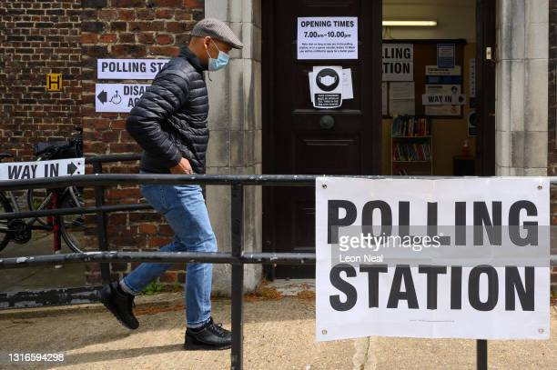 Man wearing a protective face mask enters a polling station on May 06, 2021 in London, United Kingdom. Local elections are being held across England...