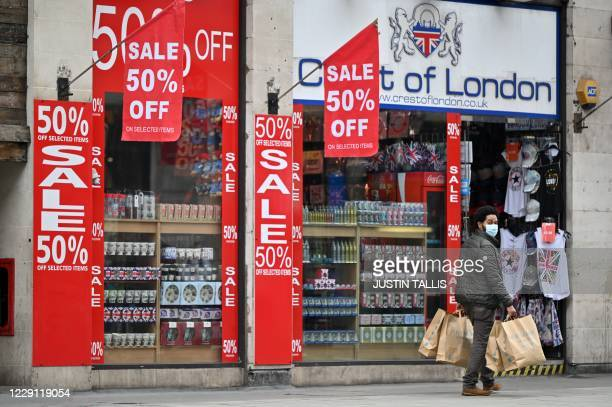 Man wearing a protective face mask glances back as he walks past a series of Sale signs outside a store in Oxford Street in London, on October 17 as...