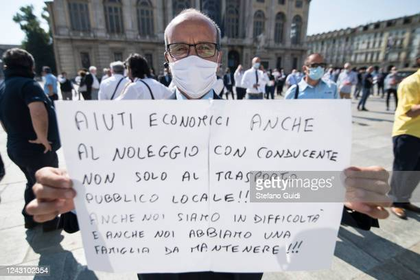 A man wearing a protective face mask holds up a sign during a demonstration by bus drivers against the Italian Government for the economic problems...