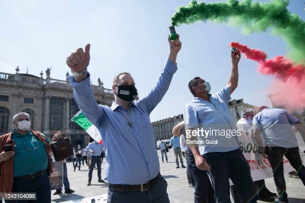 A man wearing a protective face mask lets off a colored smoke bomb during a demonstration by bus drivers against the Italian Government for the...