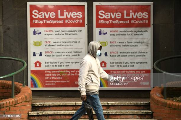 Man wearing a protective face mask passes a board displaying information how to restrict the spread of coronavirus covid-19, in central Nottingham in...