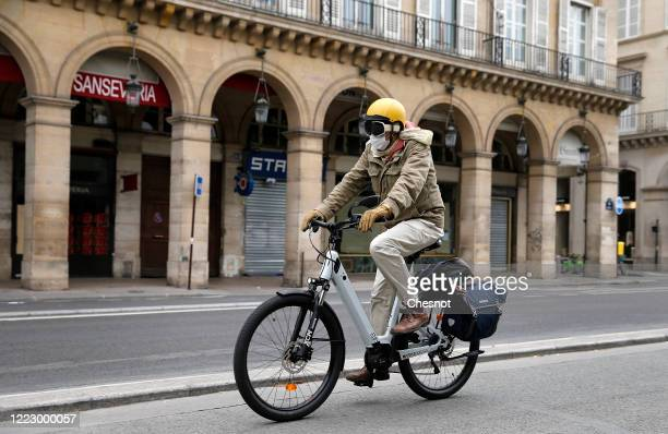 A man wearing a protective face mask rides his electric bicycle in the deserted and carfree rue de Rivoli as the lockdown continues due to the...
