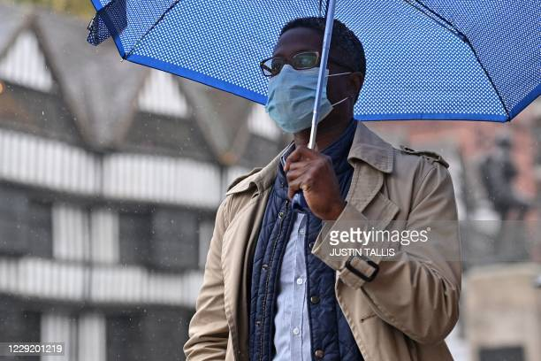 Man wearing a protective face mask, shelters from the rain under an umbrella as he walks along Holborn in central London on October 21 as the...