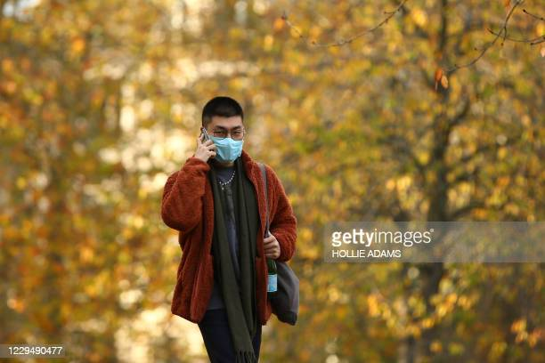 Man wearing a protective face mask speaks on the phone as he walks beneath the autumn colours in Green Park in London on November 6 as the second...