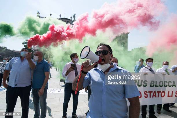 A man wearing a protective face mask speaks with a megaphone as colored smoke bombs are let off in the background during a demonstration by bus...