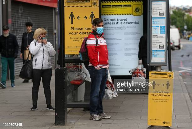 Man wearing a protective face mask waits at a bus stop surrounded by information on social distancing in Camden in central London on May 11 as life...