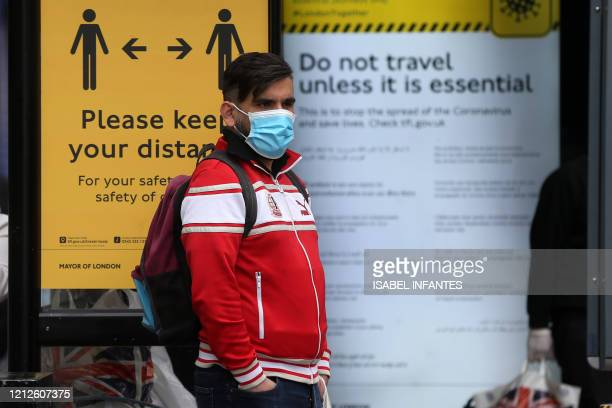 A man wearing a protective face mask waits at a bus stop surrounded by information on social distancing in Camden in central London on May 11 as life...