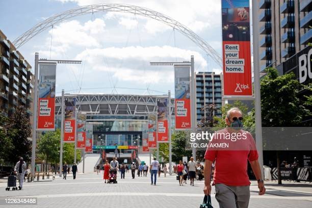 Man wearing a protective face mask walk down Olympic Way away from Wembley Stadium in London on July 12 the day that Wembley should have hosted the...