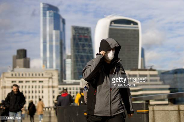 A man wearing a protective face mask walks across London Bridge as Britain braces itself for an increase in cases of the Coronavirus on March 11 2020...
